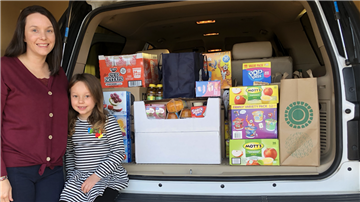 April Byrd and her daughter Maelee with food donations for Dixon Road's Backpack Buddies.  Mrs Byrd'