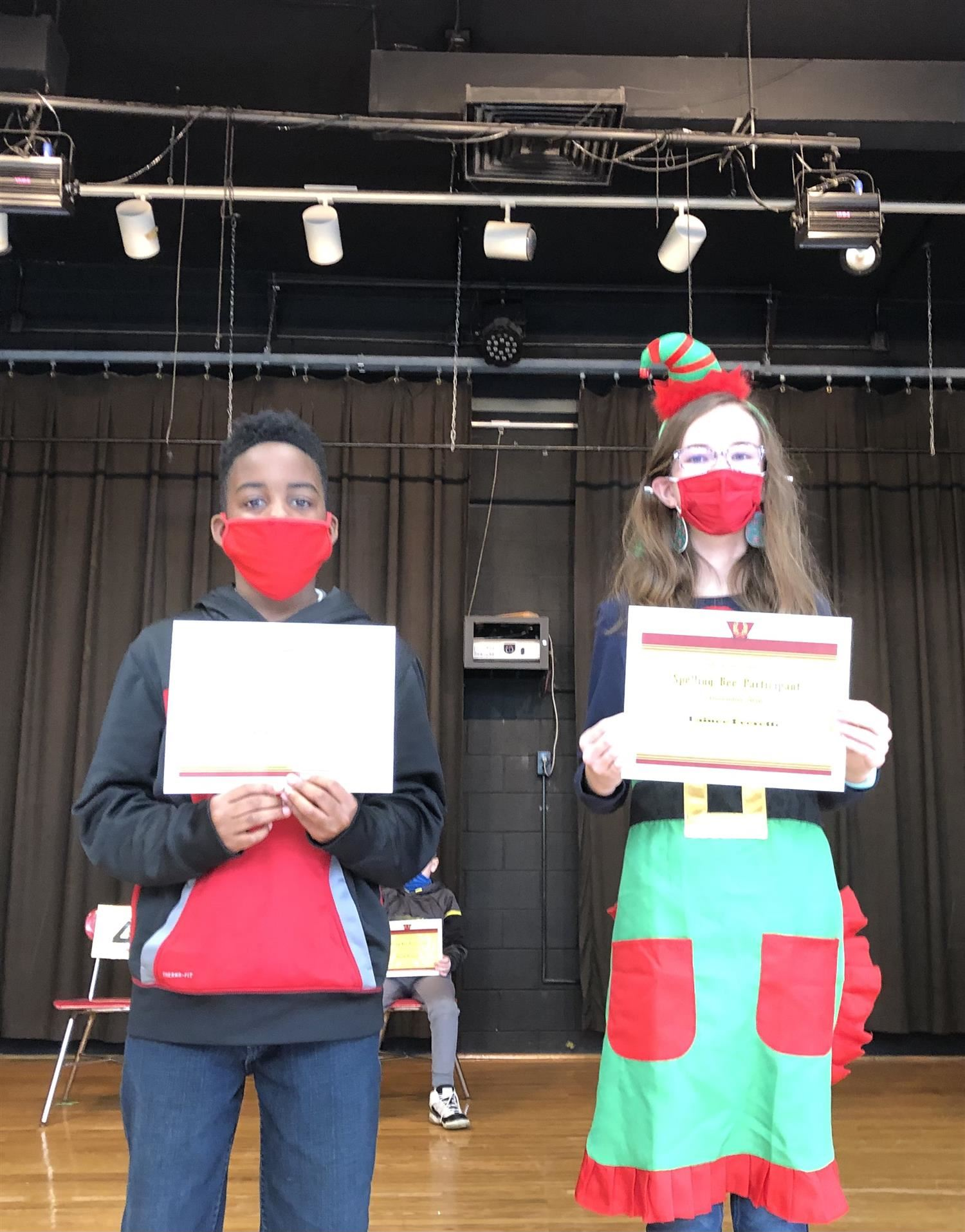 two students holding their spelling bee certificates