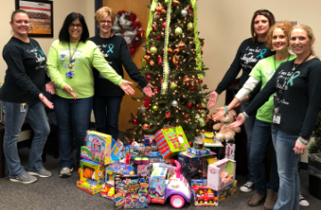 Photo of several staff members and toys collected for the Ronald McDonald House.