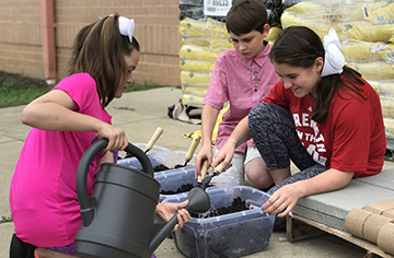 Dixon Road Elementary students working together on the soil for the new plants.