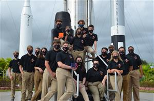 The CubeSat Launch Initiative team standing in front of rockets at NASA