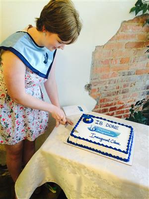 IB student Emma Lampe cutting the Cake at the Inaugural IB Banquet.