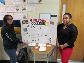 Image of two students standing by a trifold college display