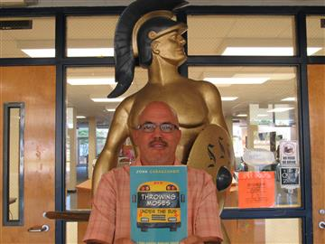John Cabascango holding his book Throwing Moses Under the Bus:  A High School English Teacher looks