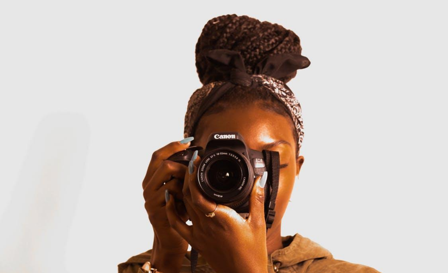 Image of a young woman looking through a camera  aimed directly forward
