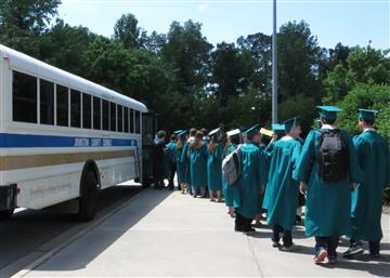 Students line up to board the bus for the Grad Walk.