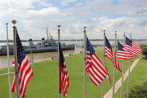 Image of American flags in the foreground with the USS Louisiana in the background